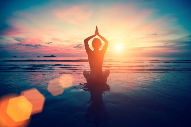 Woman in a meditation pose on the beach at sunset