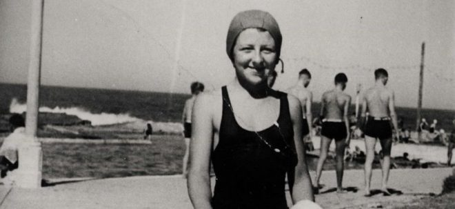 Old black and white photo of woman at the beach in bathing cap and swimsuit