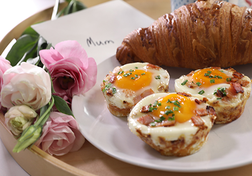 Hash brown egg nests, croissant and pink roses on a tray