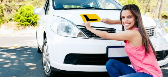 Girl putting learner plates on a white car